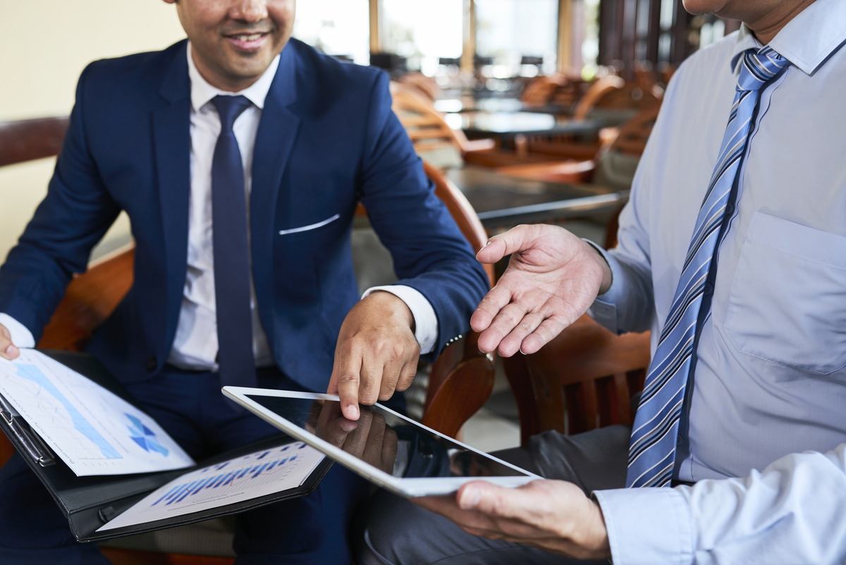 Close-up of two businessmen sitting at the table pointing at touchscreen of digital tablet and working remotely in cafe