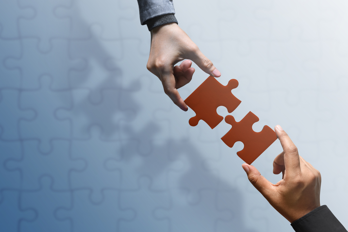 Business Partnership or Teamwork Concept. Hands of two People Try to Fit or Conncet Jigsaw Puzzle Piece Together. Top View