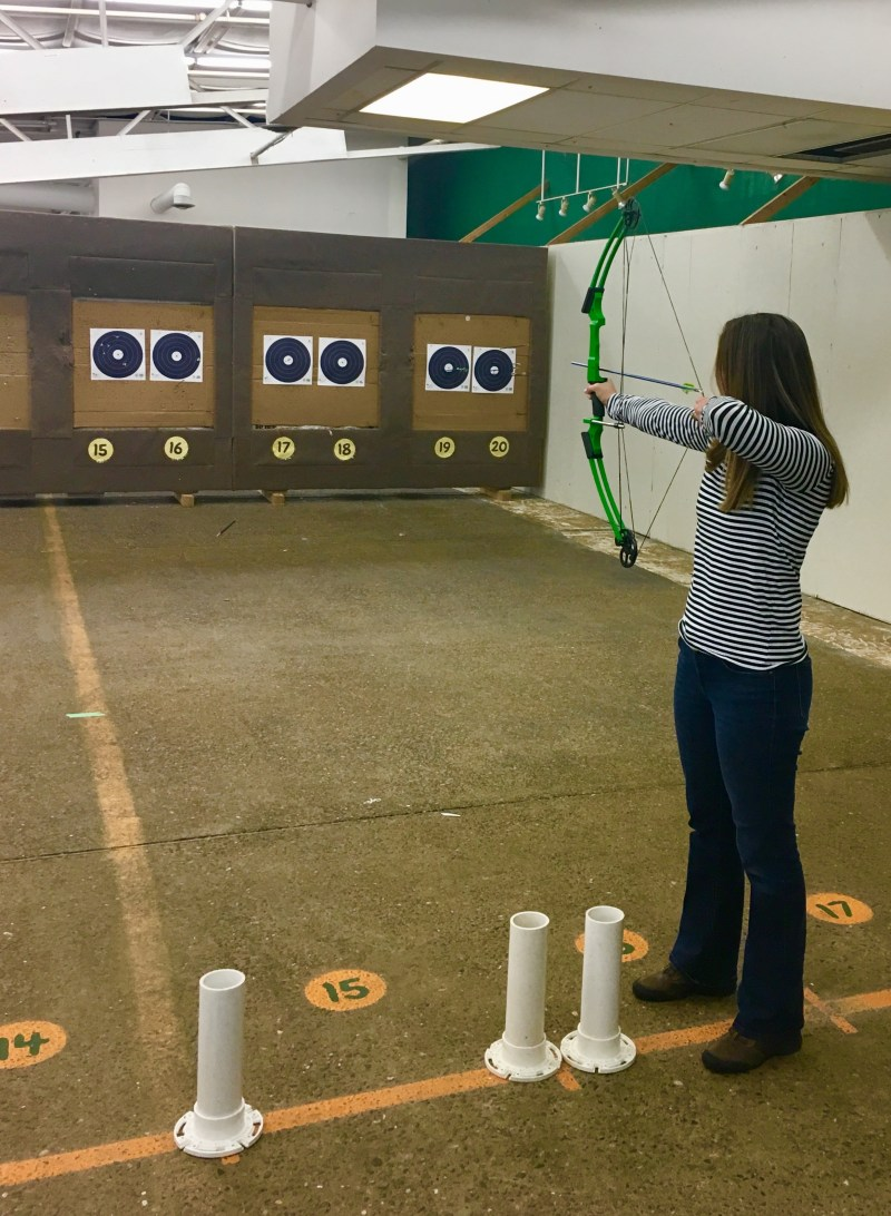Women aiming at target with bow raised.