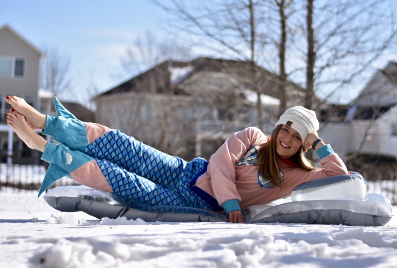 Girl dressed in mermaid costume laying on inflatable float in snow.