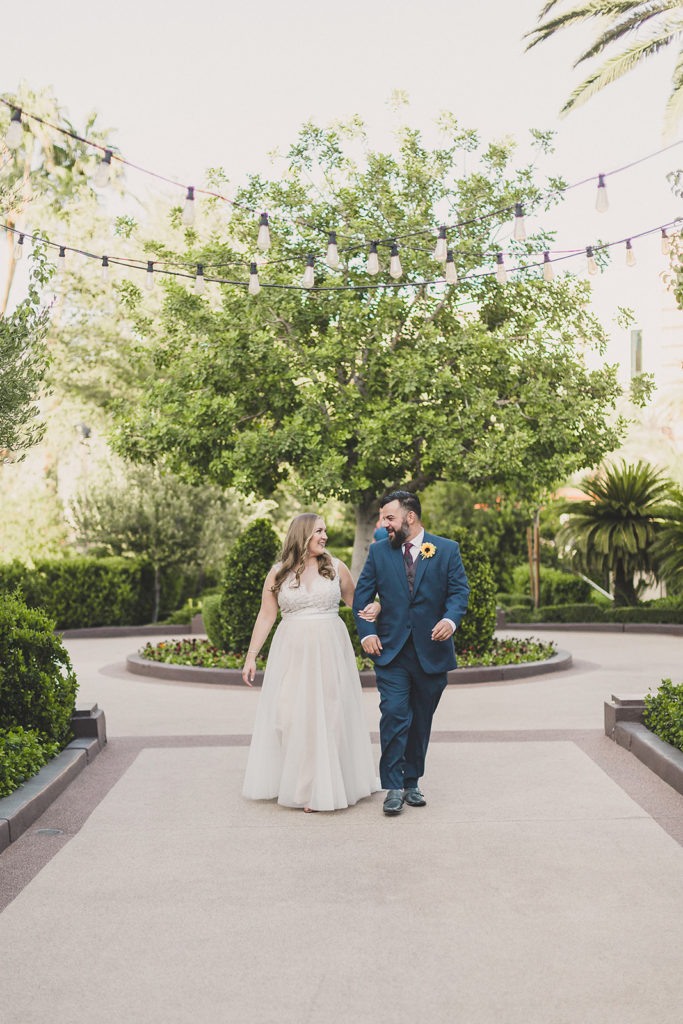bride and groom walk around MGM poolside with Taylor Made Photography