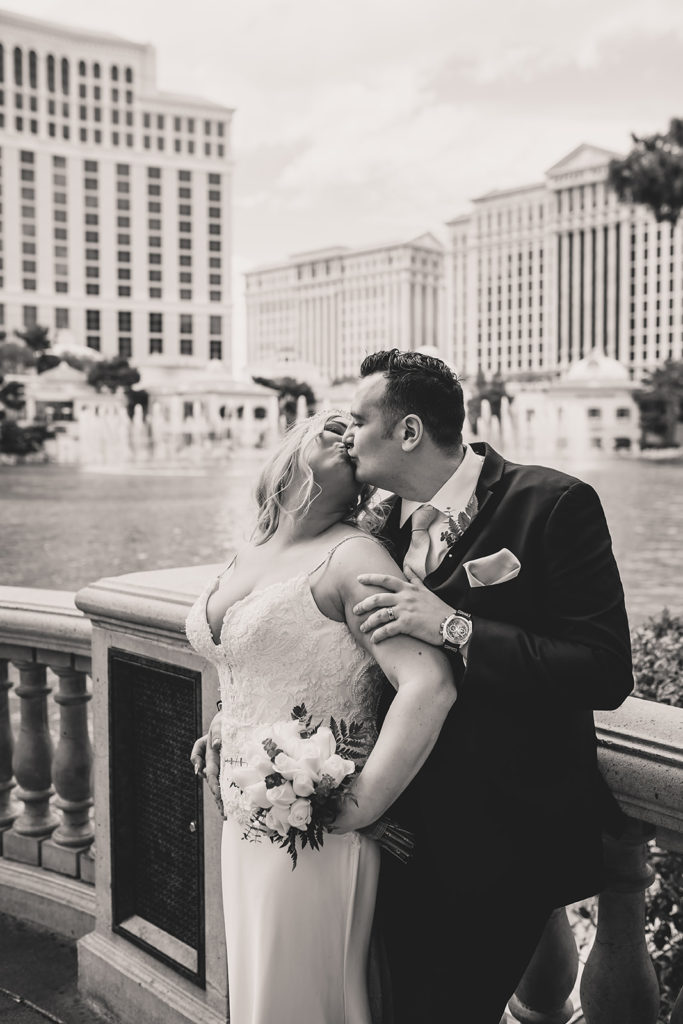 newlyweds kiss by Lake Las Vegas with Taylor Made Photography