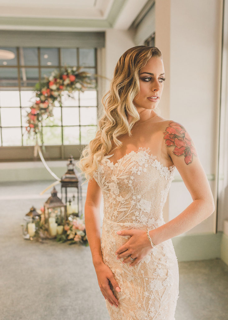 bride looks out window while touching lace on wedding gown photographed by Taylor Made Photography