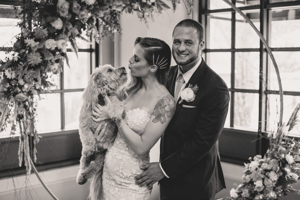 bride and groom pose with dog at Park MGM photographed by Taylor Made Photography