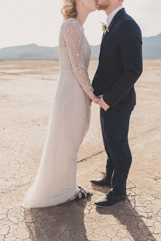 bride and groom kiss after eloping in El Dorado's Dry Lake Bed