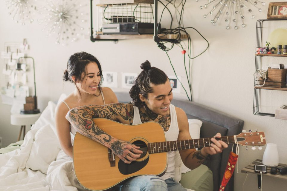 couple plays guitar during lifestyle portraits with Taylor Made Photography