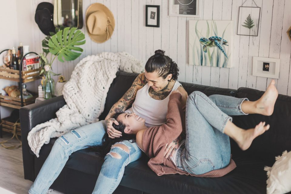 couple relaxes at home on couch during lifestyle portraits with Taylor Made Photography