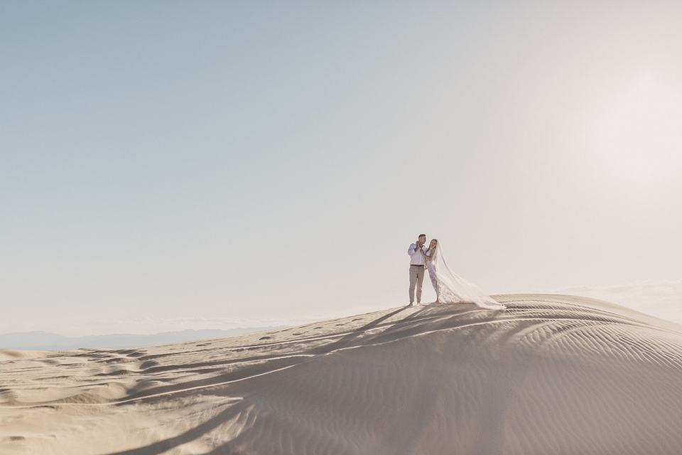 bride and groom hug on sand dunes in Las Vegas photographed by Taylor Made Photography