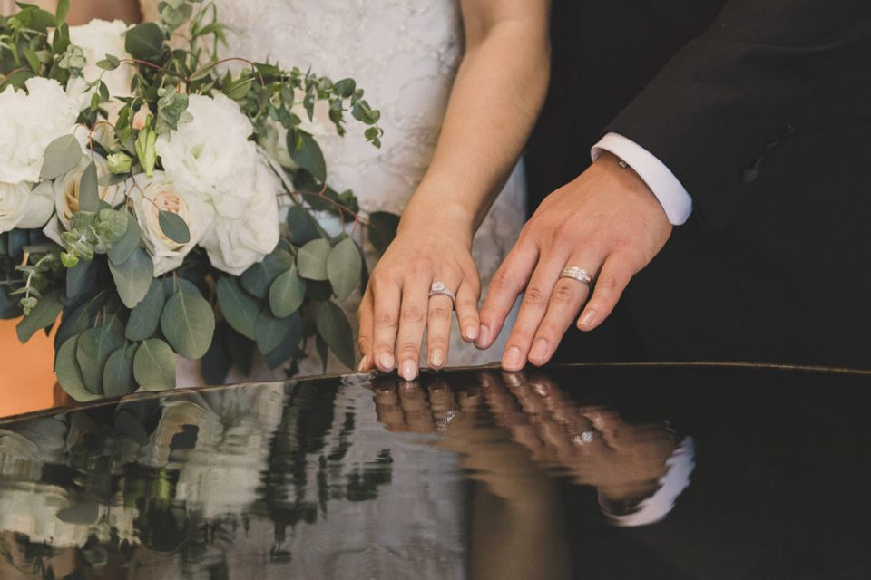 bride and groom show off wedding rings photographed by Taylor Made Photography