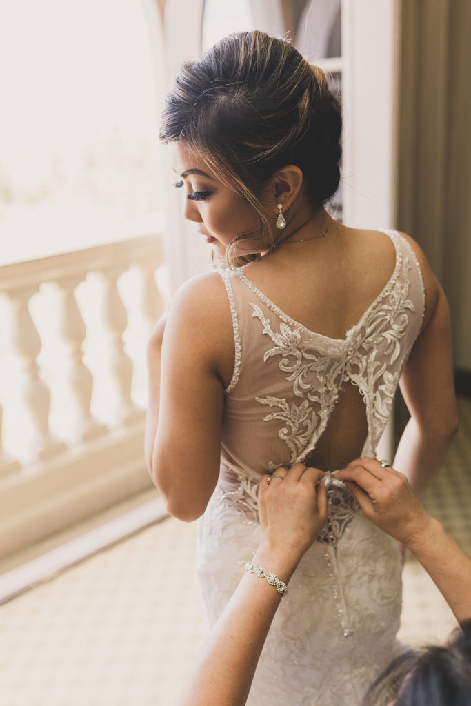 bridesmaid helps bride into wedding gown in Las Vegas photographed by Taylor Made Photography