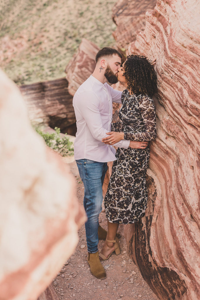 couple kisses among rocks photographed by Taylor Made Photography