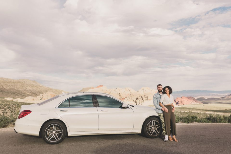 couple poses by white car in Las Vegas photographed by Taylor Made Photography
