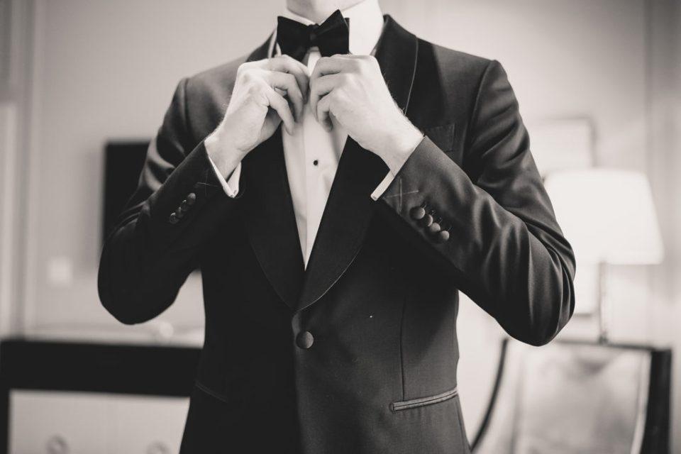 groom ties bowtie before wedding day in Las Vegas