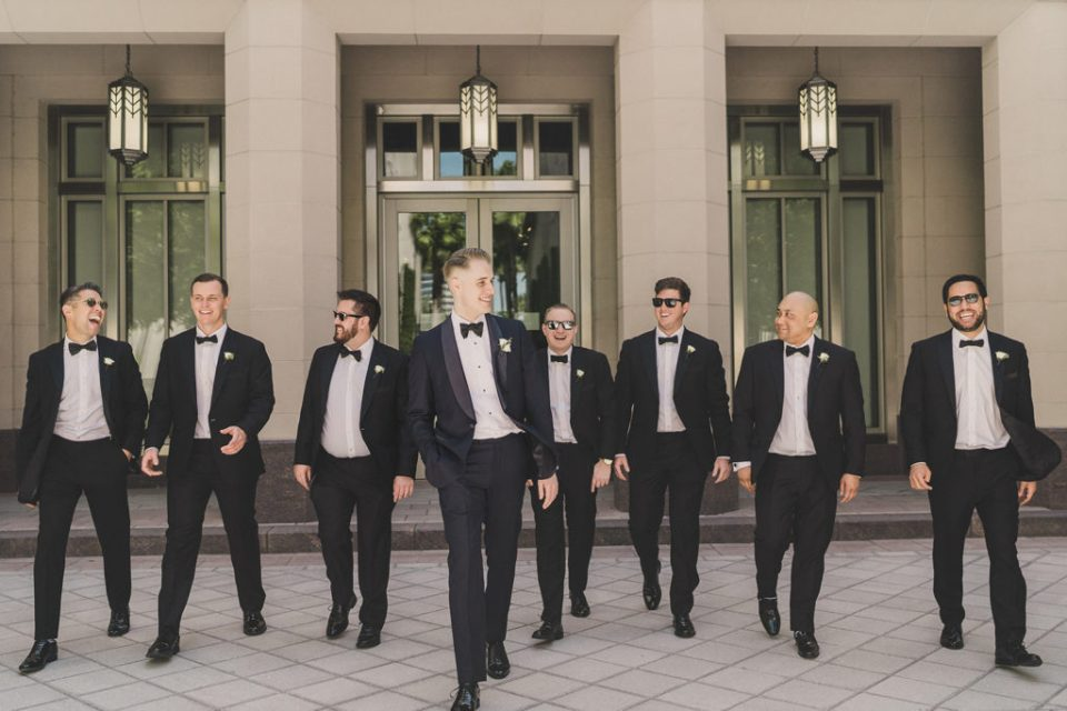 groom and groomsmen walk outside the Smith Center for the Performing Arts