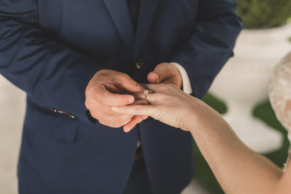 groom places ring on bride's finger during elopement in Las Vegas with Taylor Made Photography
