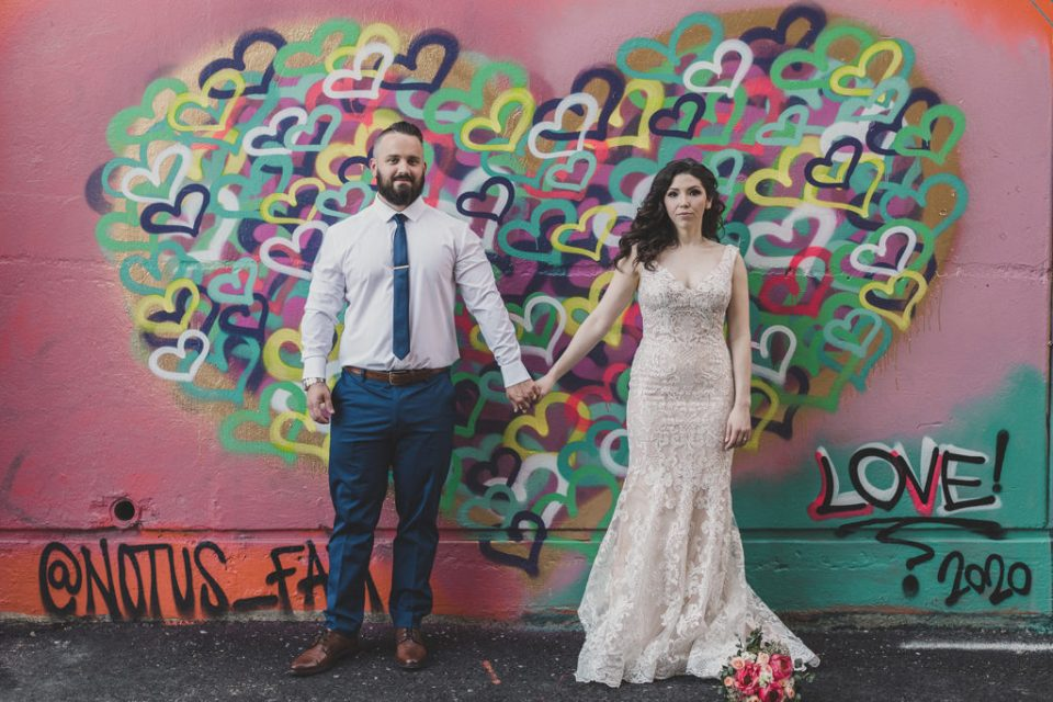bride and groom hold hands in front of heart mural in Downtown in Las Vegas photographed by Taylor Made Photography