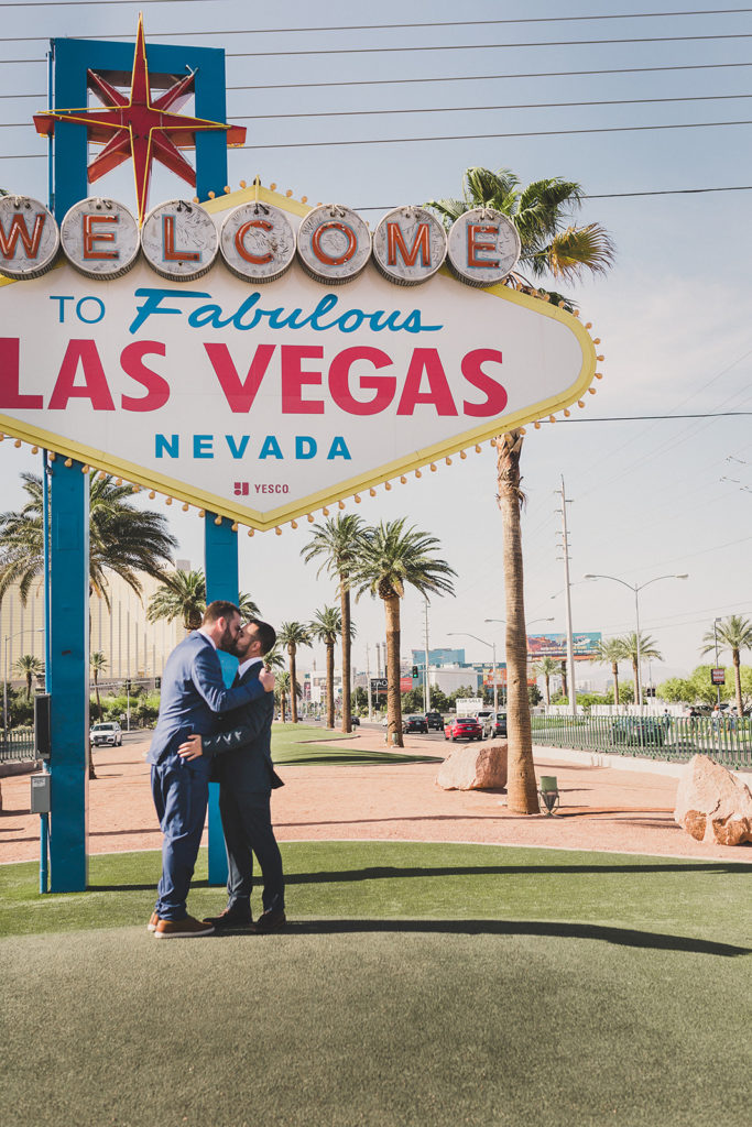 grooms kiss under Las Vegas sign with Taylor Made Photography