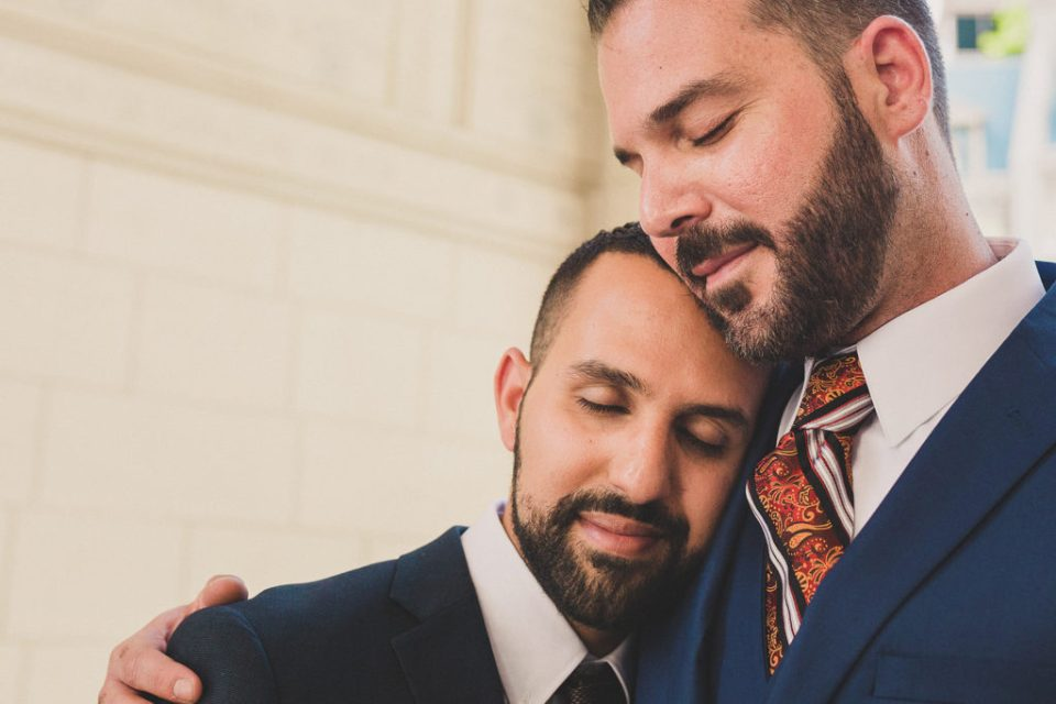 grooms embrace during Las Vegas portraits with Taylor Made Photography