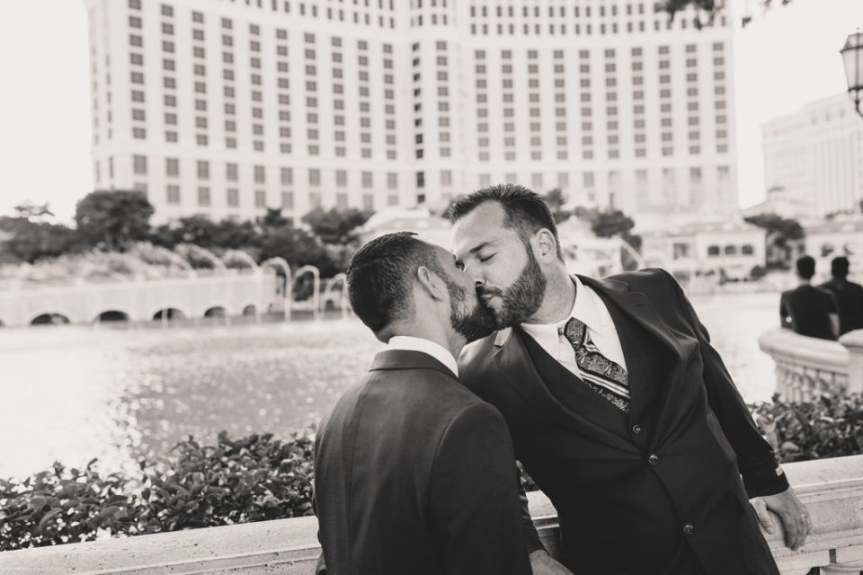 Taylor Made Photography captures grooms kissing in front of Bellagio Fountains