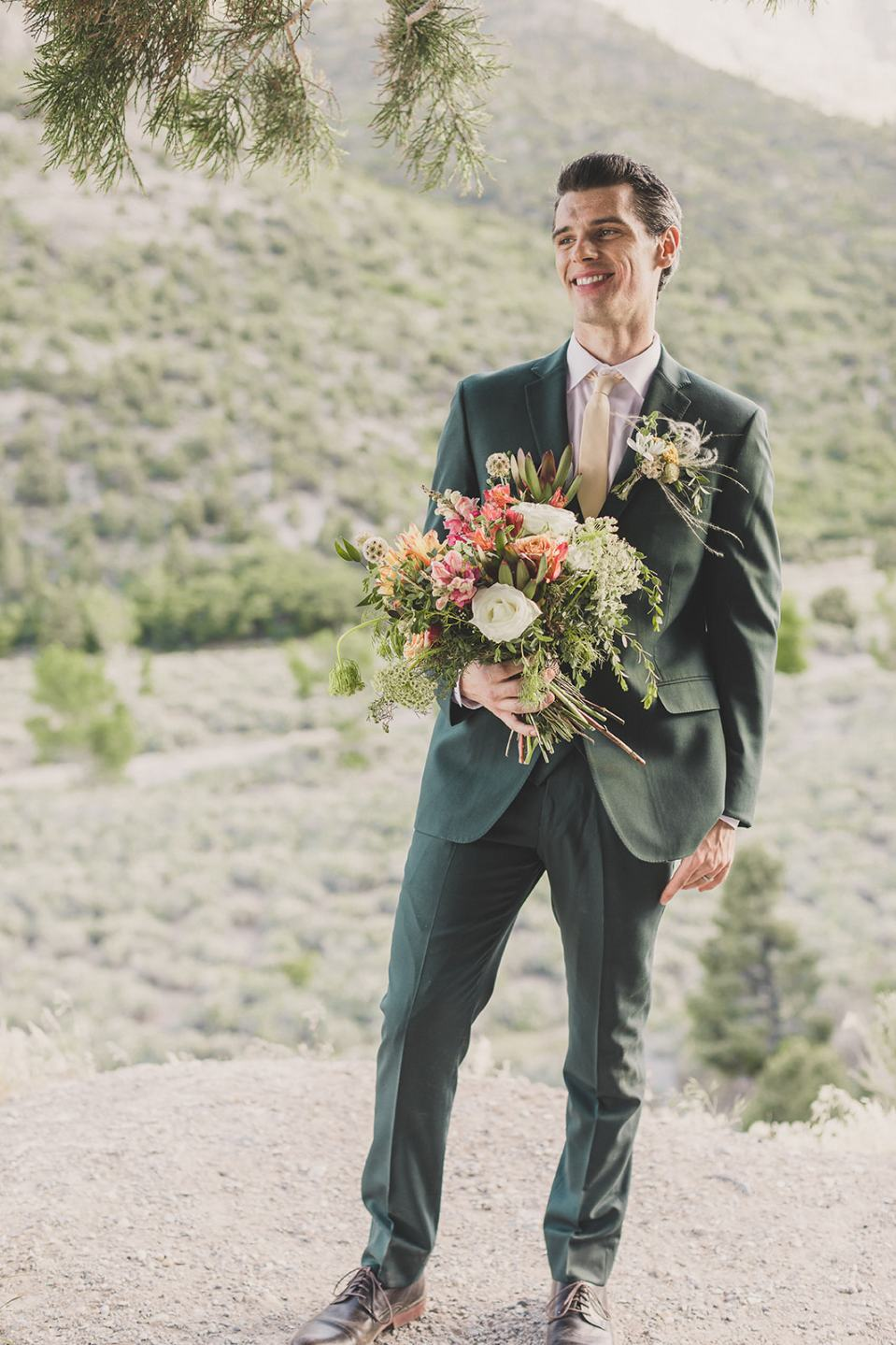 groom holds bride's summer bouquet photographed by Taylor Made Photography
