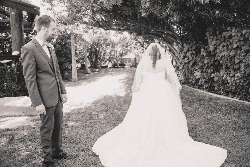 bride shows groom gown during first look at the Grove photographed by Taylor Made Photography