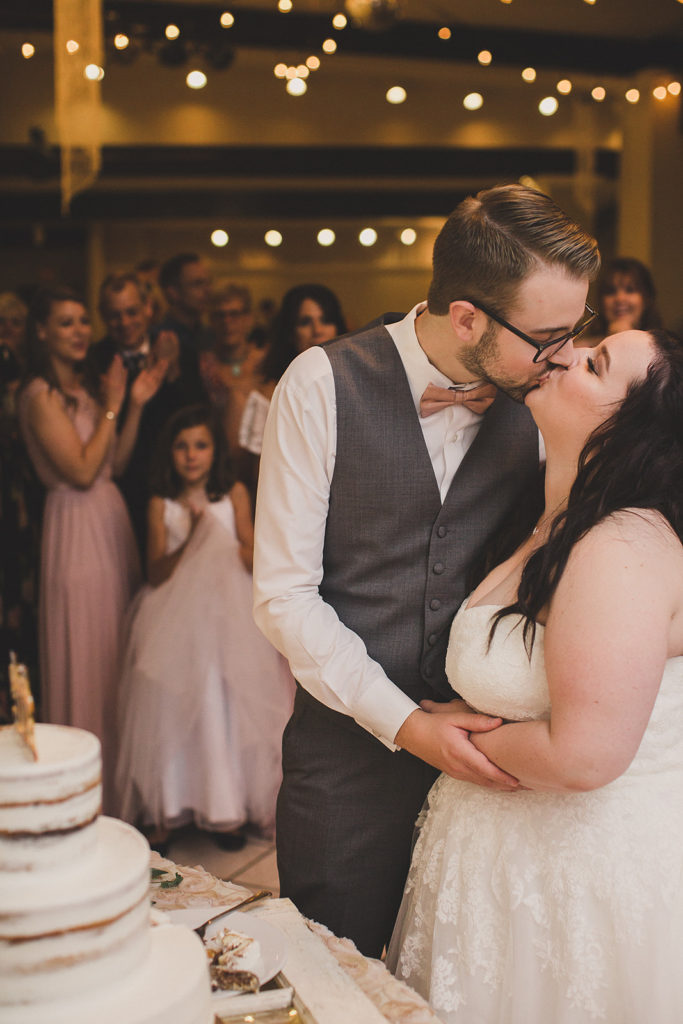 bride and groom kiss after cutting cake photographed by  Taylor Made Photography