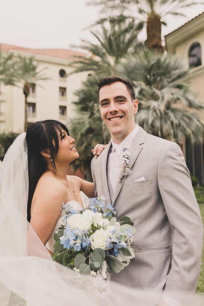 bride looks at groom while veil wraps around them at JW Marriott Las Vegas