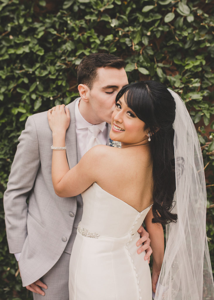 groom kisses bride on the cheek while she looks over shoulder