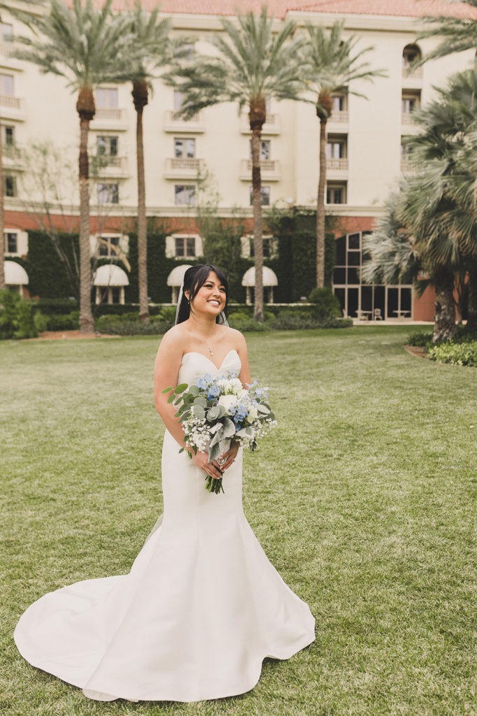 bride holds blue and white bouquet before first look