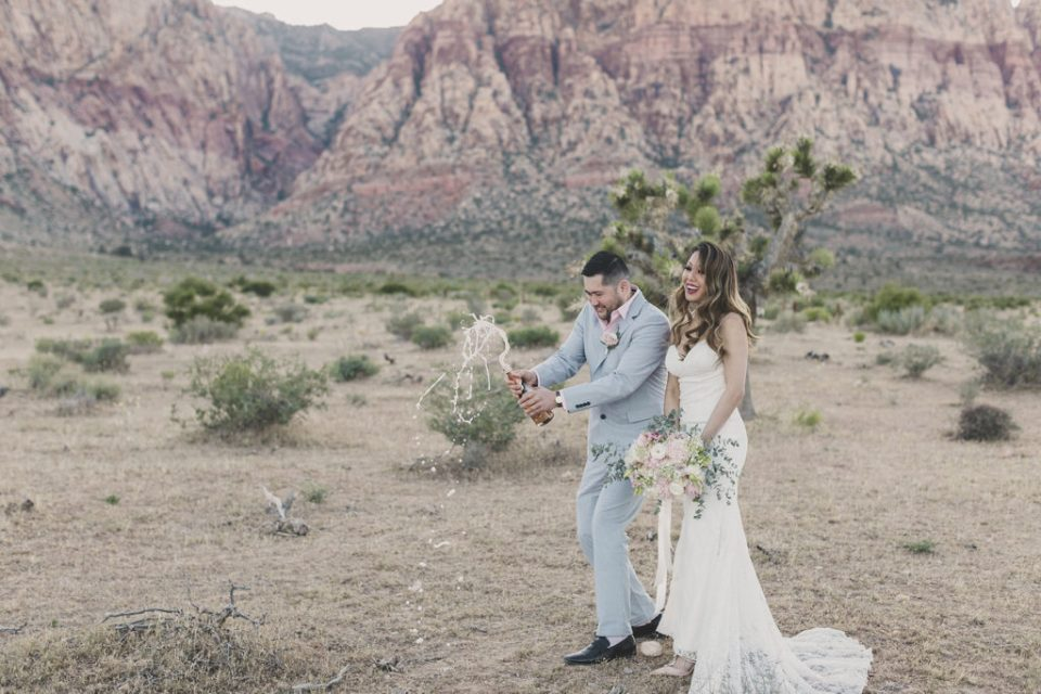 Taylor Made Photography photographs bride and groom popping open champagne in Red Rock Canyon