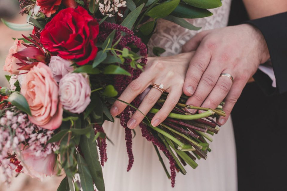 bride and groom show off wedding bands next to bridal bouquet in Las Vegas photographed by Taylor Made Photography