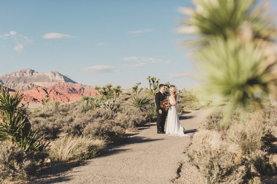 bride and groom walk to wedding ceremony in Red Rock Canyon with Taylor Made Photography