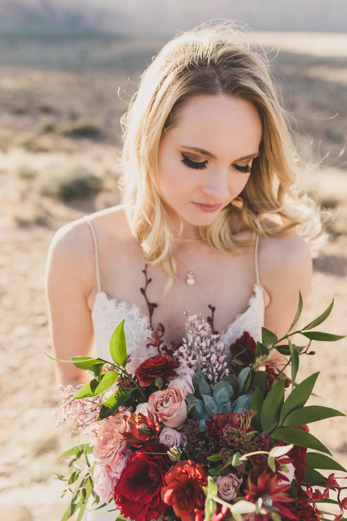 bride looks at wedding bouquet in Red Rock Canyon