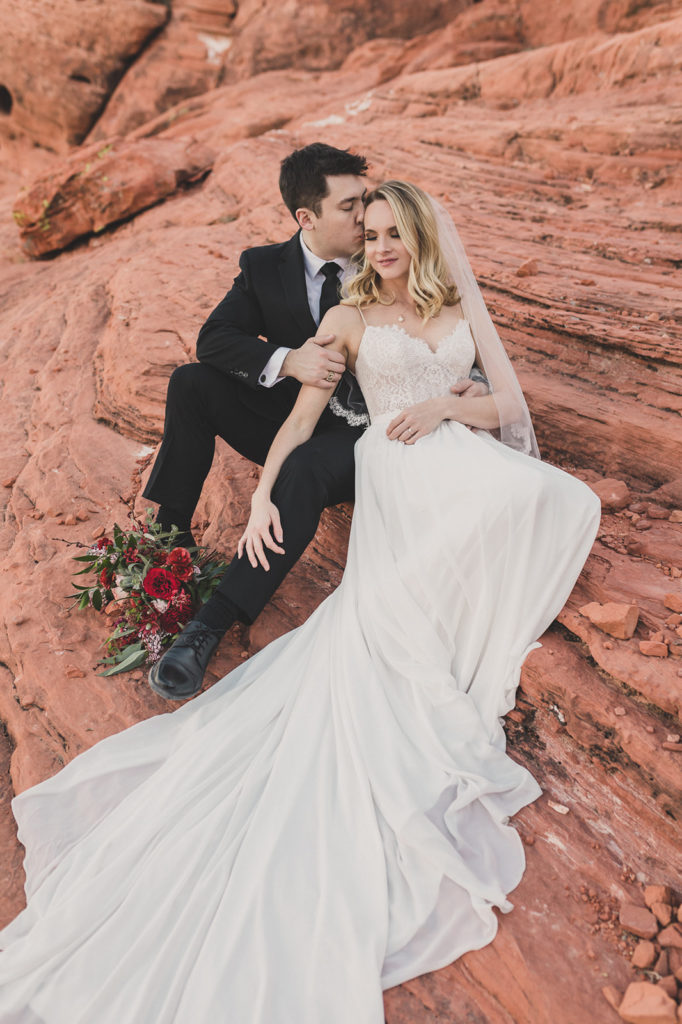 bride leans against groom in Red Rock Canyon photographed by Taylor Made Photography