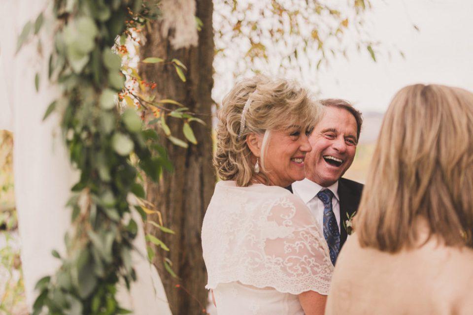 newlyweds laugh during Freestone Lodge wedding ceremony