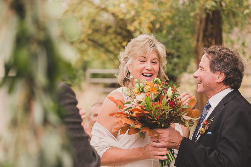 couple laughs during riverfront wedding ceremony at Freestone Lodge