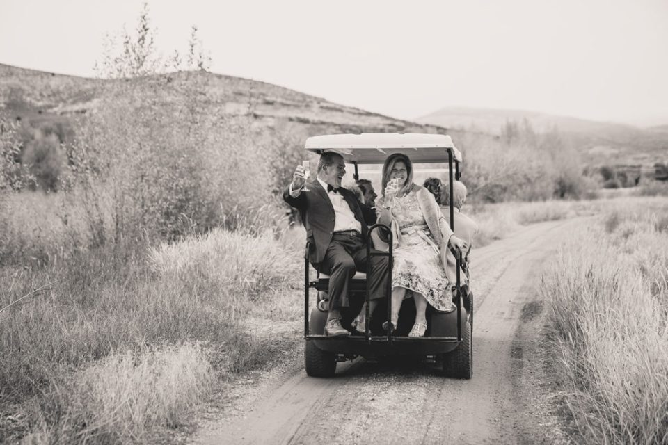 wedding guests ride up to lodge on golf cart