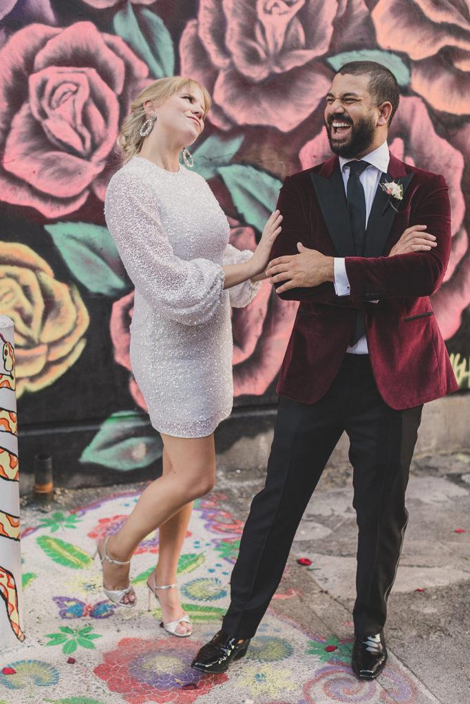 bride in modern wedding dress laughs with groom in burgundy tux