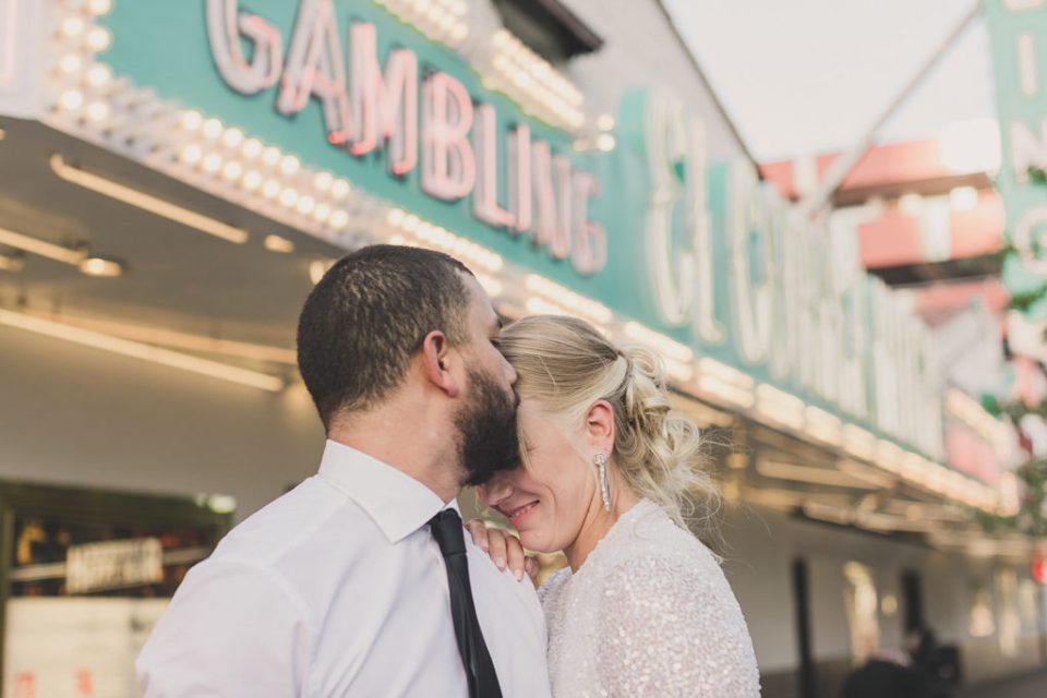 bride and groom laugh during portraits by Gambling sign in Las Vegas