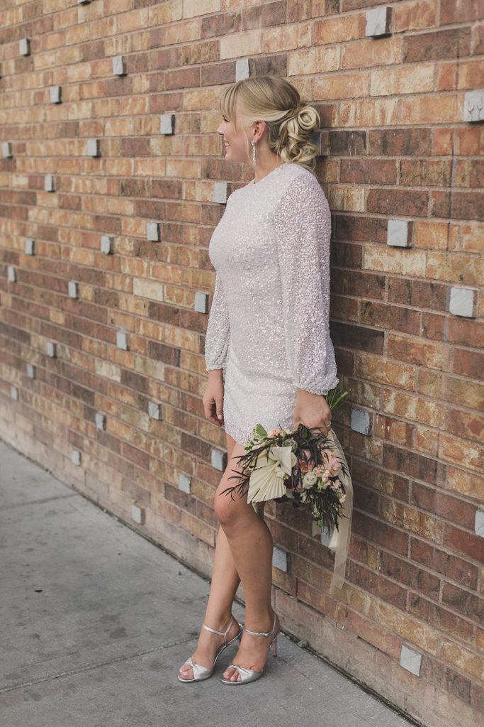 bride looks away from camera posing by brick wall with short wedding dress