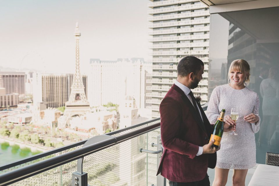 bride in short wedding dress and groom in burgundy tux pop champagne before elopement in Las Vegas