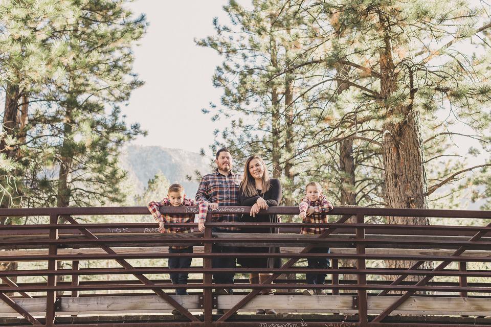 family of four poses on bridge during Las Vegas Family Portraits