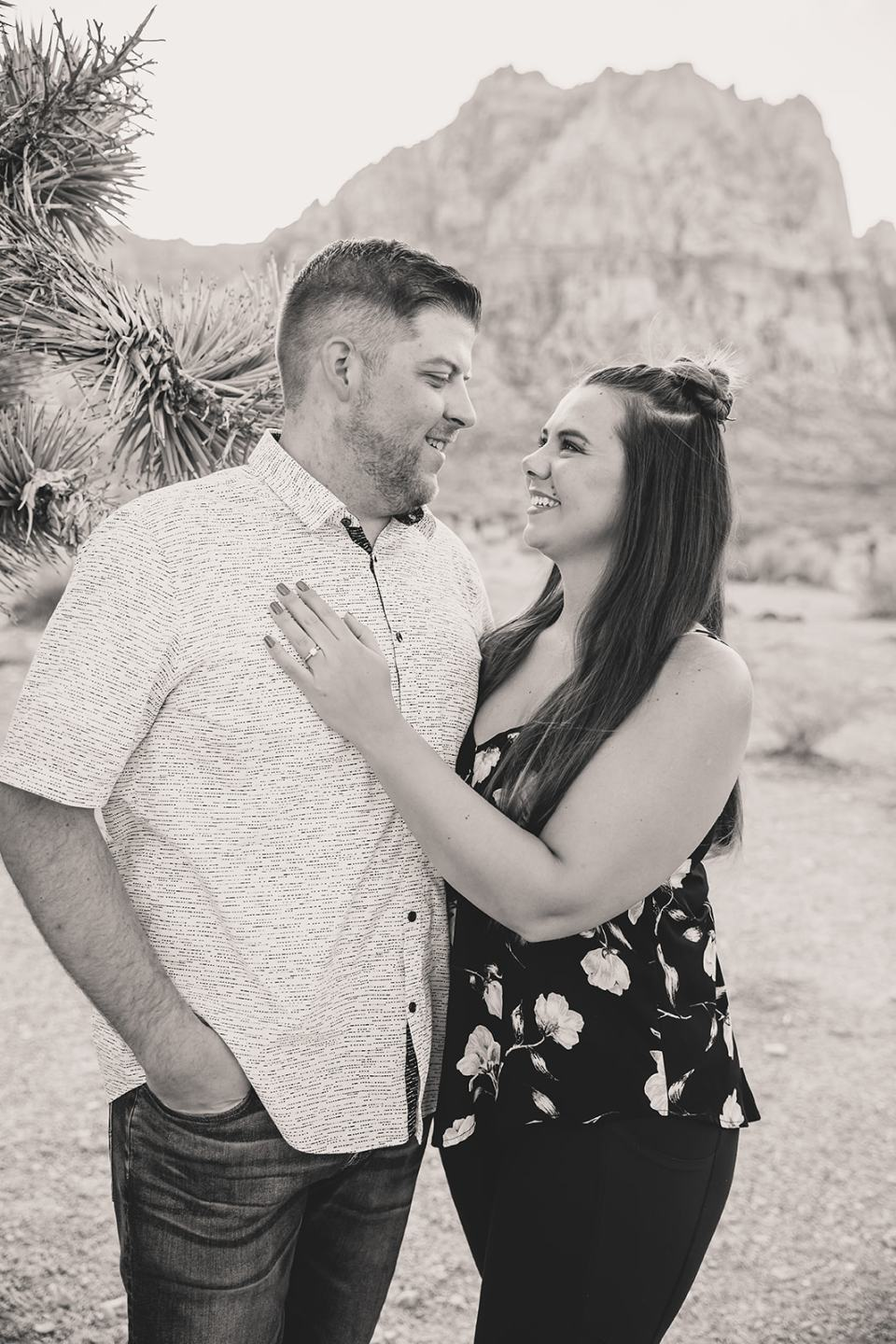 engaged couple poses by joshua tree in First Creek Canyon