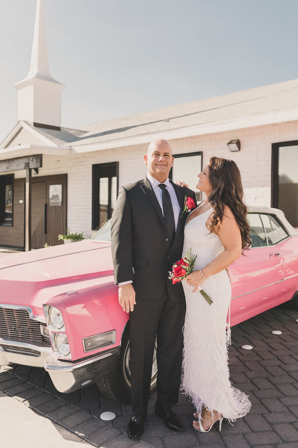newlyweds pose by pink Cadillac in Las Vegas