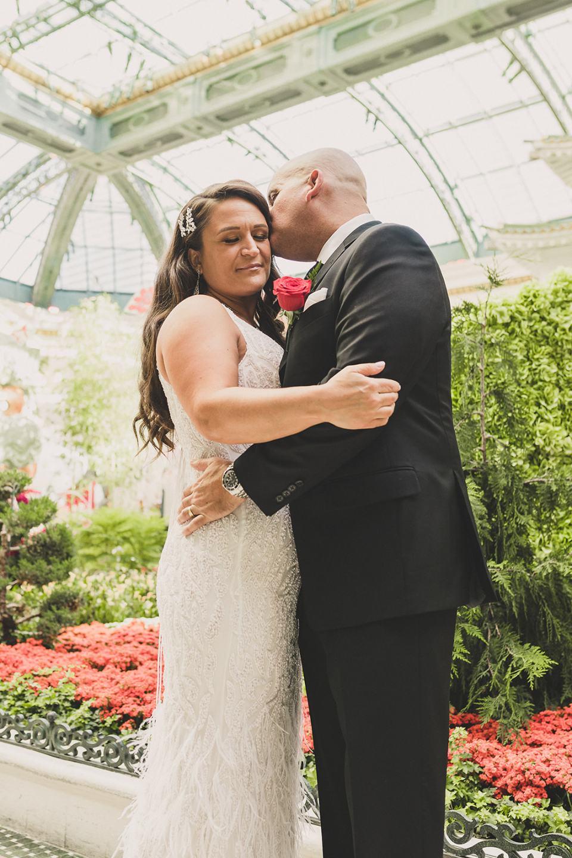 groom kisses bride's cheek in gardens at Bellagio Hotel