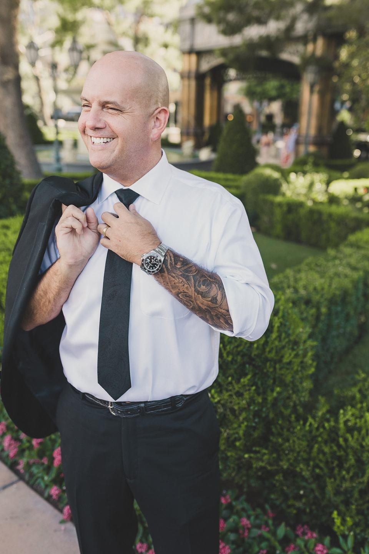 groom adjusts tie during Las Vegas elopement portraits