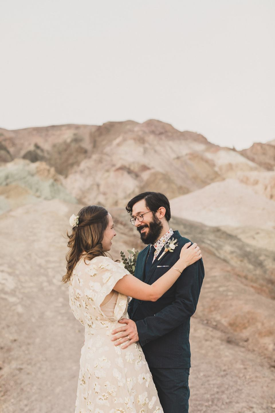 groom looks at bride with smile during wedding photos at Zabriskie Point
