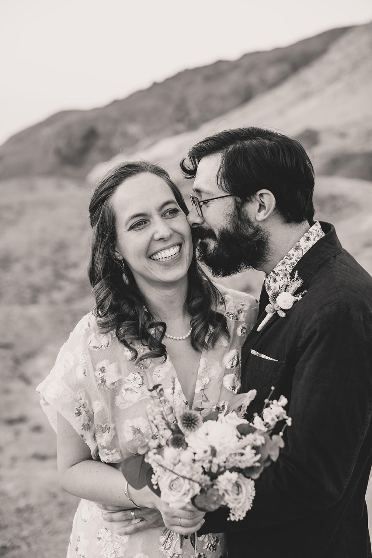 groom nuzzles bride at Zabriskie Point