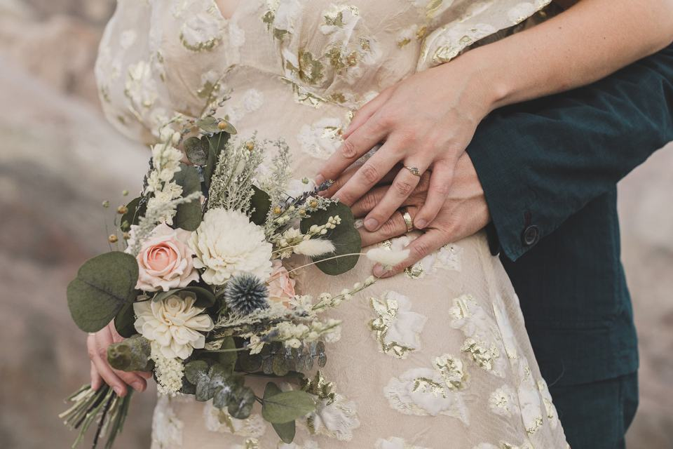 newlyweds hold hands on bride's hip