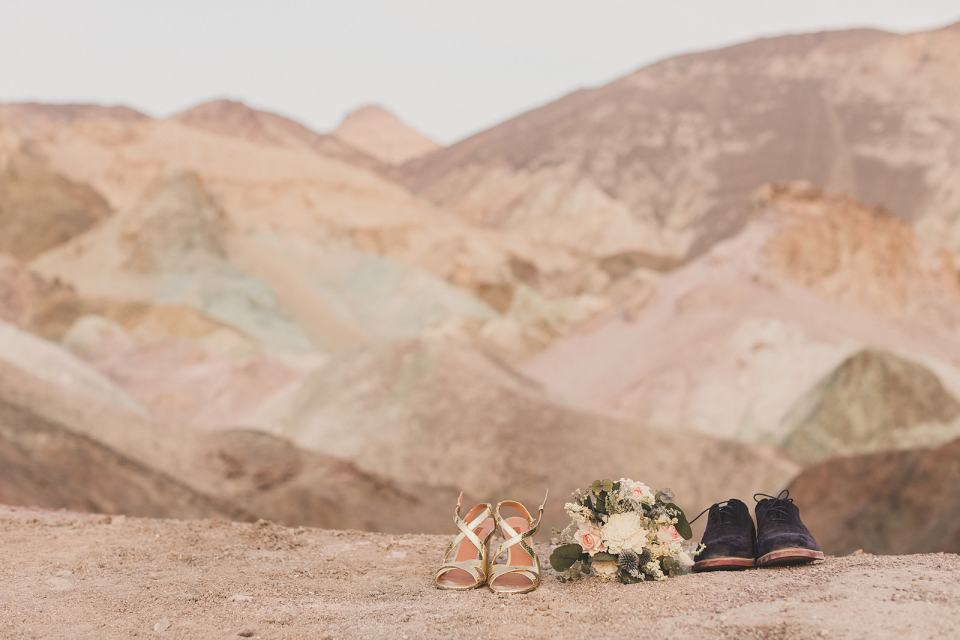 bride and groom's shoes rest on Zabriskie Point